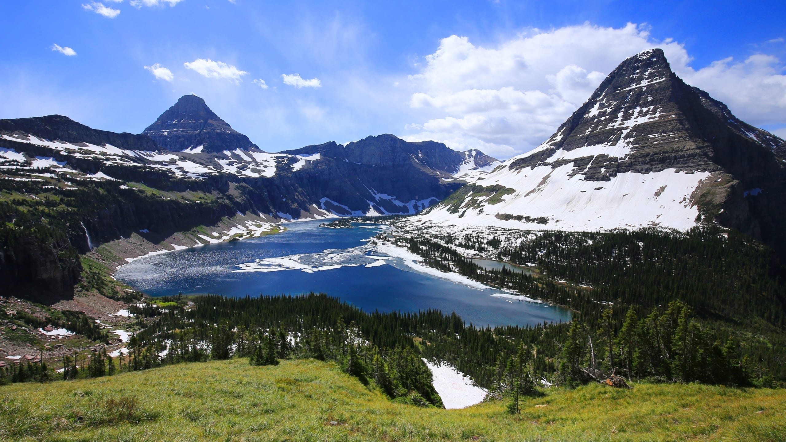 A view of a lake between two snow covered mountains in the beautiful Glacier National Park