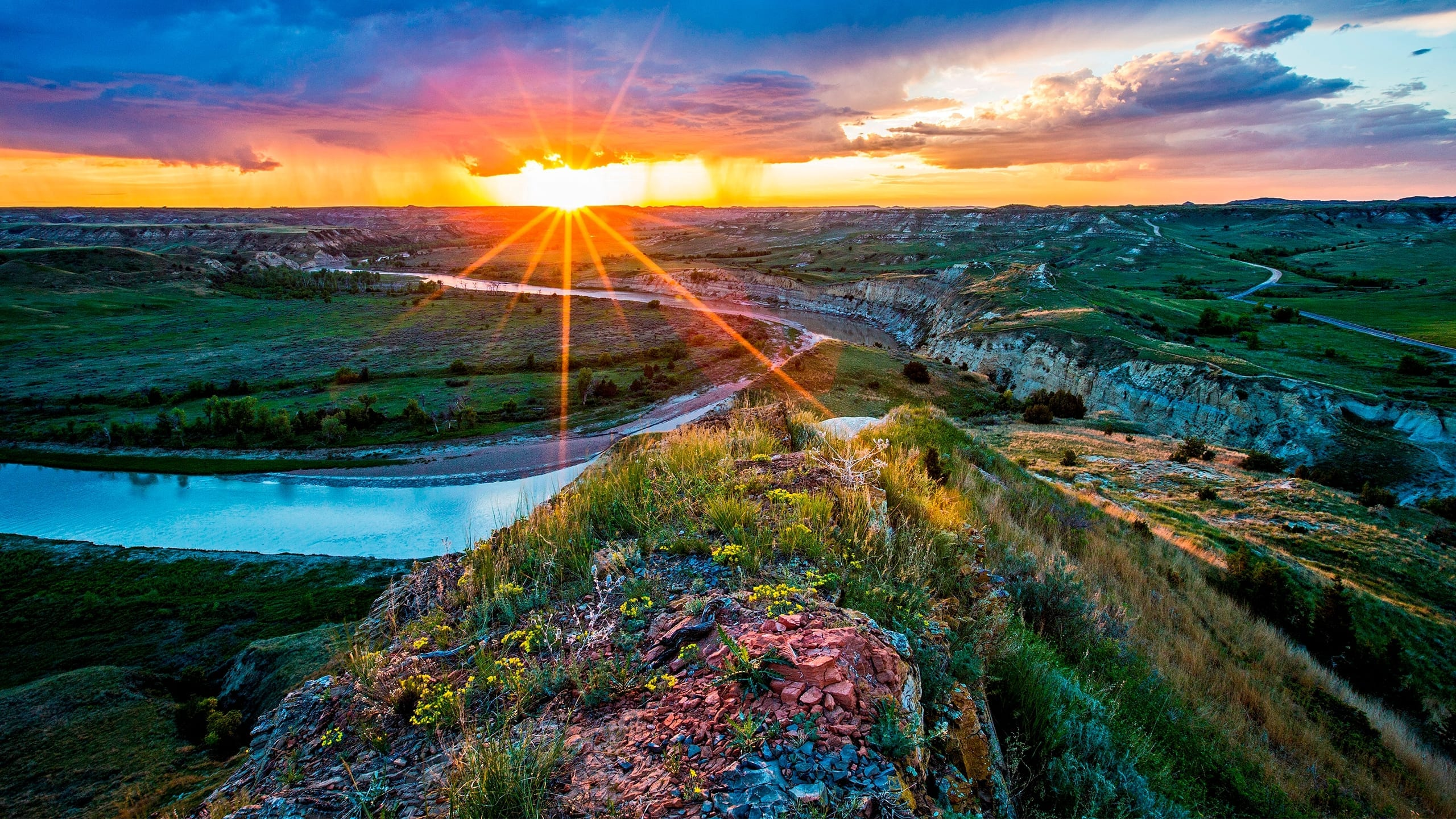 Rays from a setting sun burst through cloud to shine on a rocky butte and river down below.