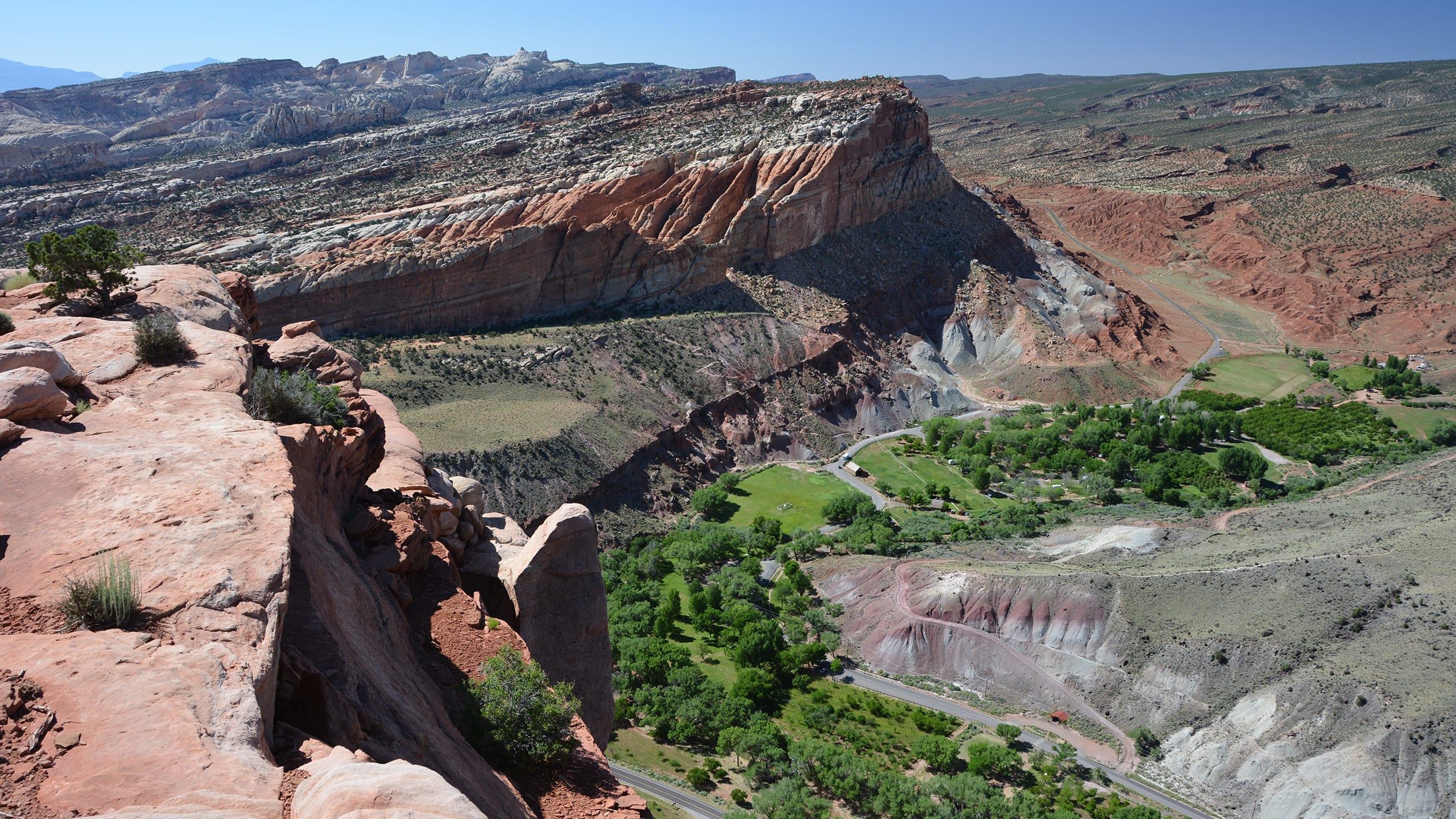 View from sandstone rim with a green valley, gray slopes, and red cliffs and blue sky.