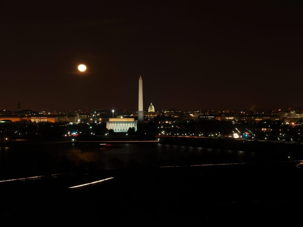 A view across the Potomac River of the Lincoln Memorial, the Washington Monument, and the U.S. Capitol at night.