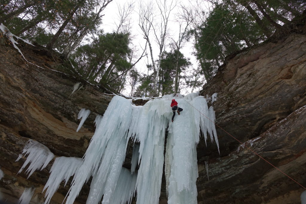 Ice Climber near the top of a curtain and column of ice. The ice is forming out of and hanging off sandstone rocks. Trees are on top of the cliff.