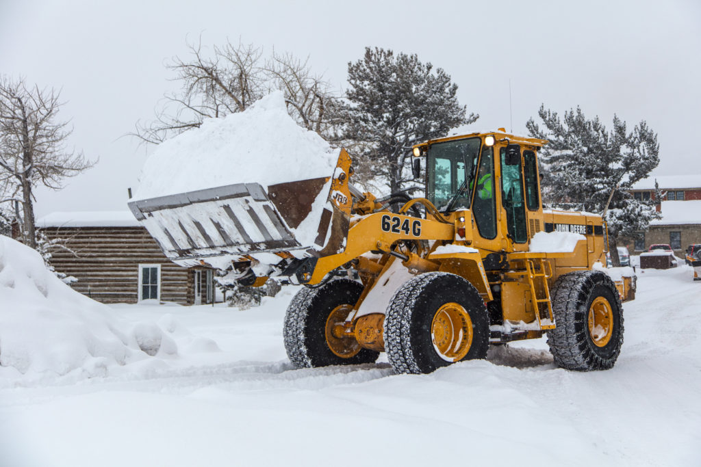 A front loader has a bucket full of snow