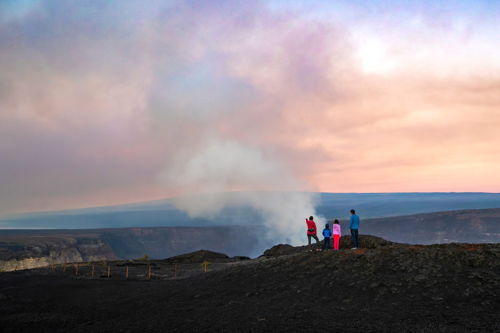 A family watches a plume of gas and steam rise from Kīlauea just after sunrise from the Keanakākoʻi viewing area.