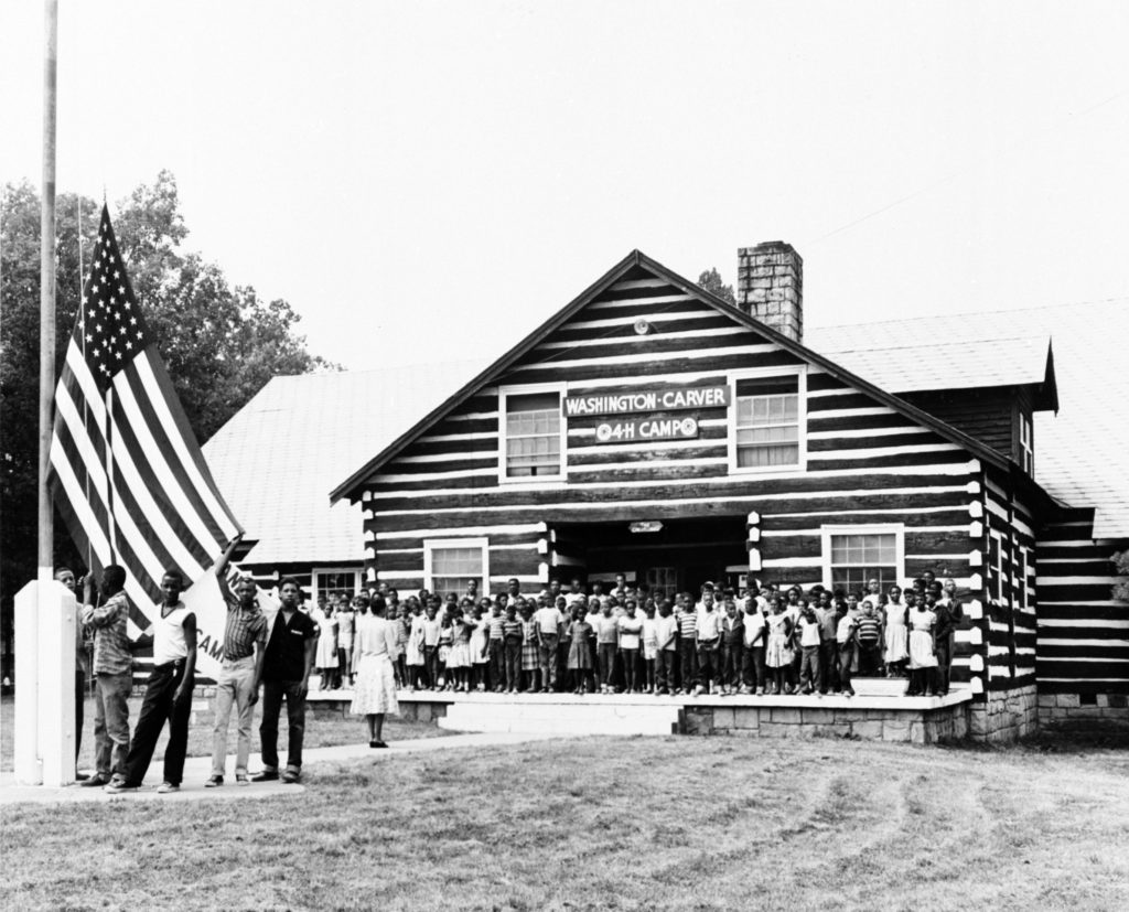Historic black and white photo of children posing in front of a 4-H camp lodge