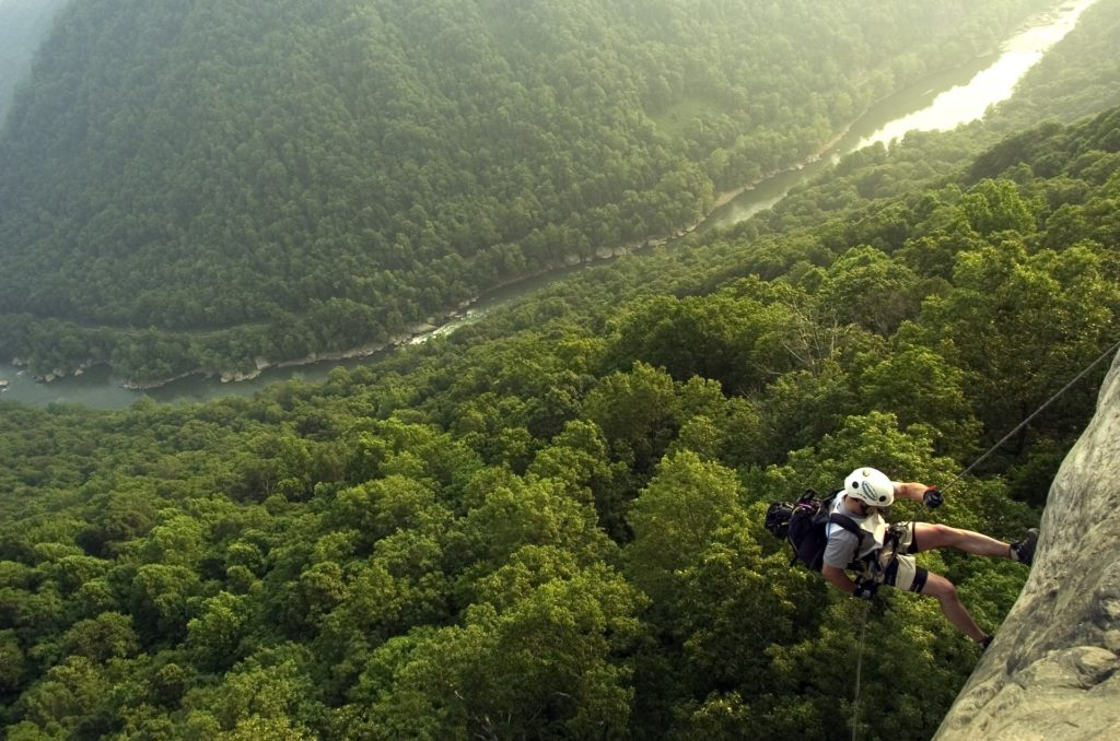 A climber descends a rockface over the gorge in New River Gorge National Park & Preserve