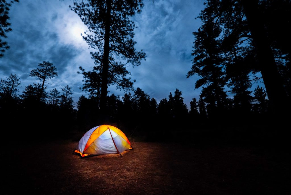 A tent lite up at night with the moon in the clouds surrounded by trees