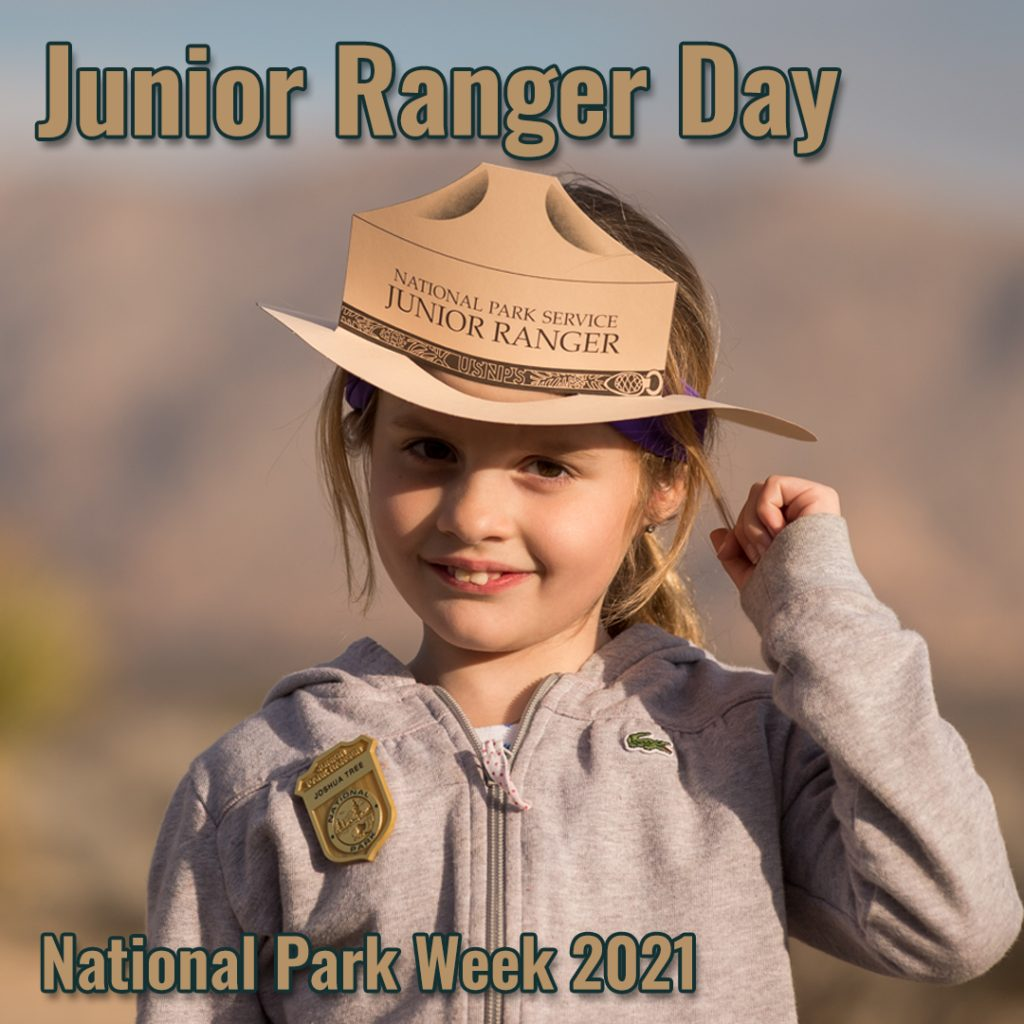 A young female child stands with her pin and a paper cutout Park Ranger hat