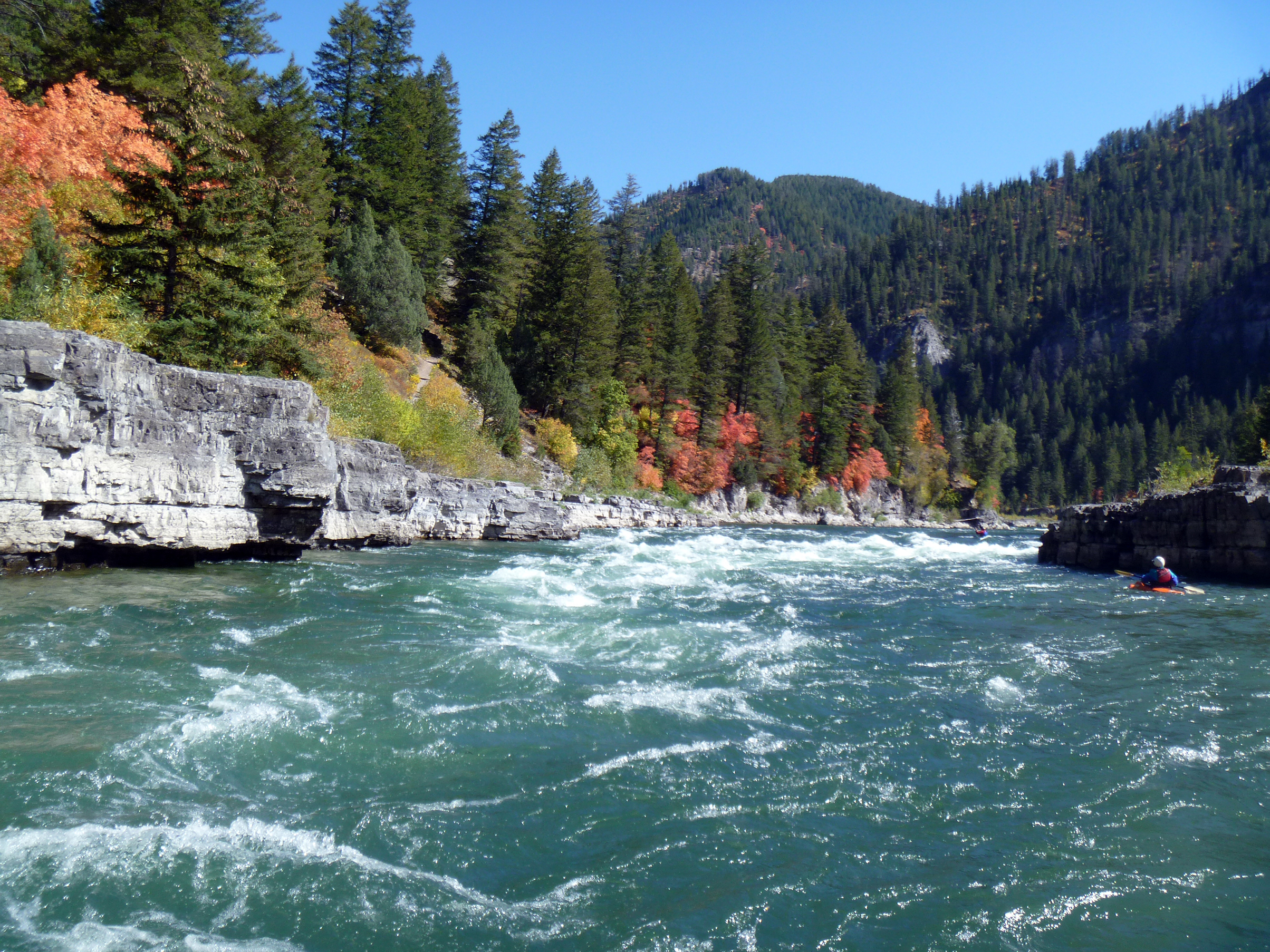 A kayaker floats the snake river through rapids with cliff facings on the river sides, fall colored trees and mountains in the background.
