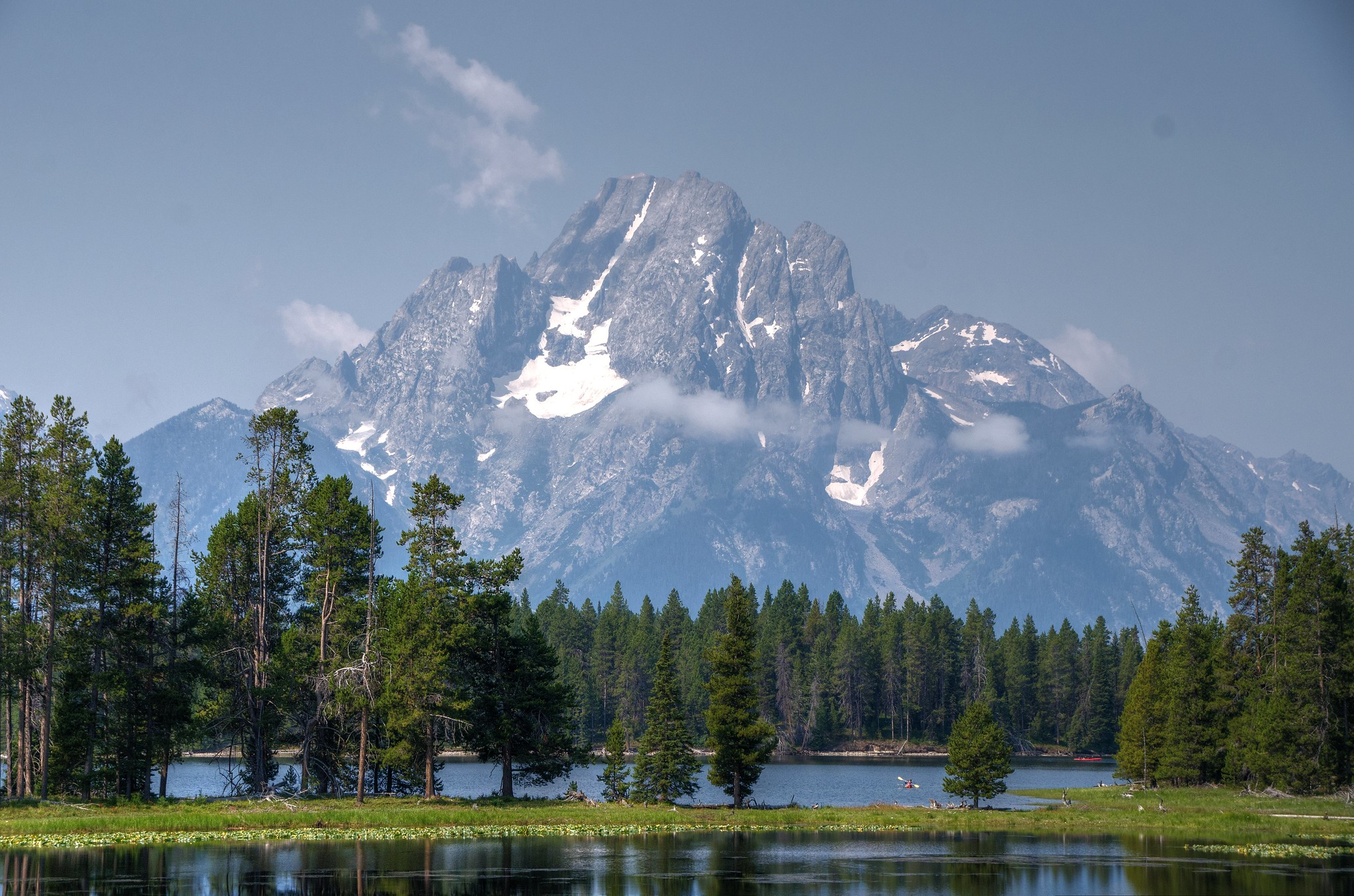 A view of Mount Moran with trees surrounding Heron Pond in front taken from the Hermitage Point Trail