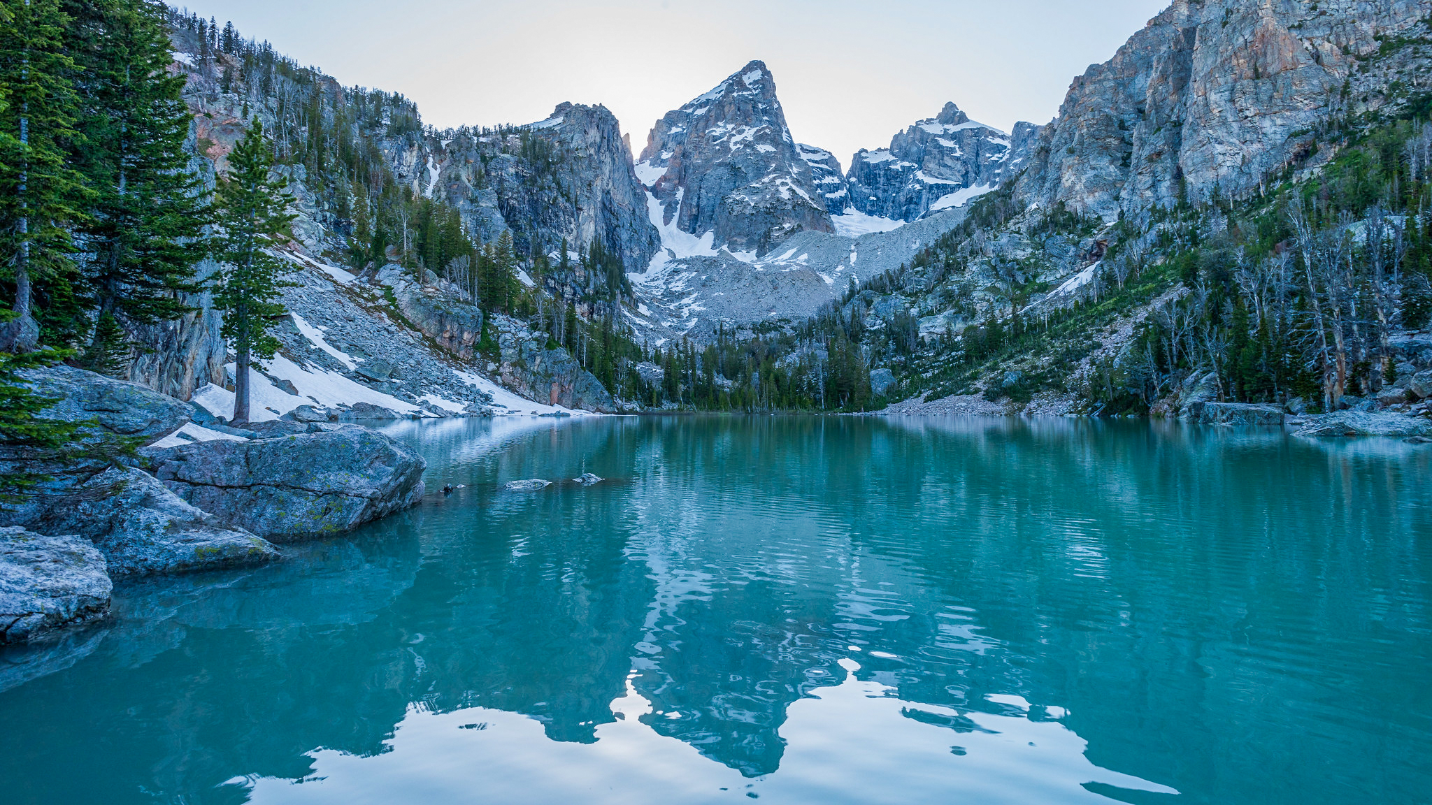 A lake with clear blue glacier water, green trees around the lake and the tall snowy mountain peaks surrounding the lake like an amphitheater.