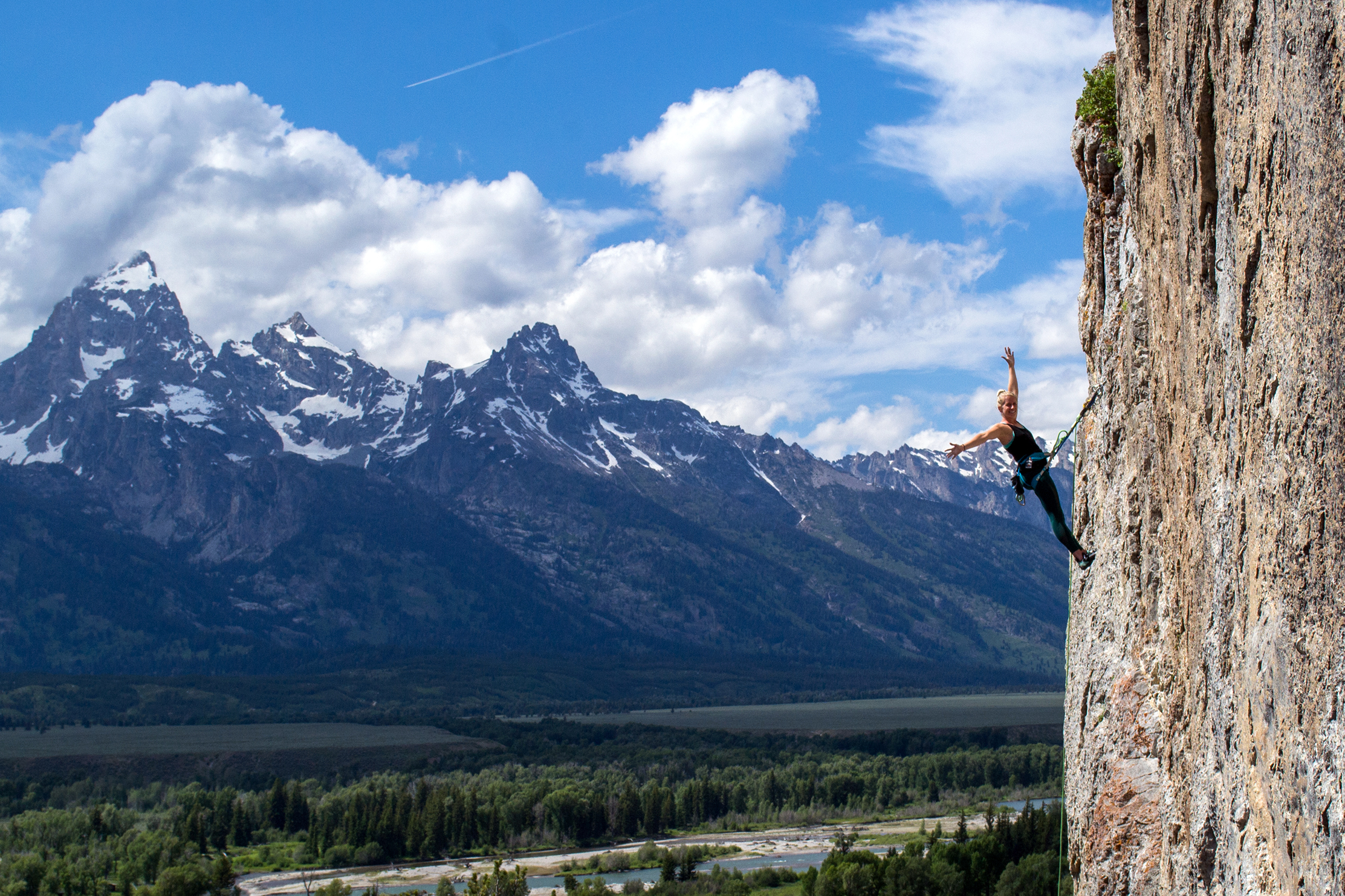 Female climber showing off with a view of the Tetons